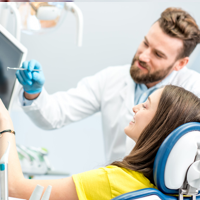 Dentist and patient both pointing to monitor
